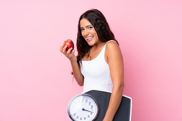Mujer joven sobre rosa aislado con máquina de pesaje y con una manzana