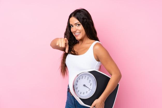 Mujer joven sobre rosa aislado sosteniendo una máquina de pesaje y apuntando hacia el frente