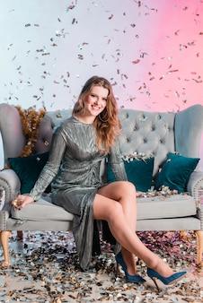 Mujer joven en el sofá con copa de champán