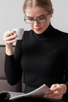 Mujer joven en el sofá tomando café