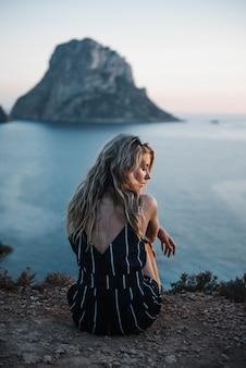Mujer joven solitaria con cabello rubio sentado junto al mar disfrutando de su tiempo de paz