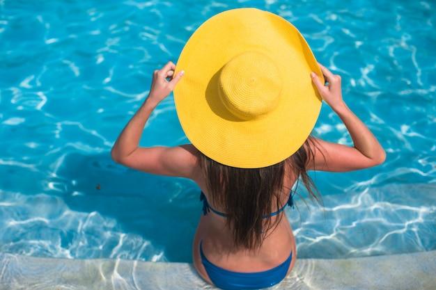 Mujer joven con sombrero amarillo relajante en la piscina