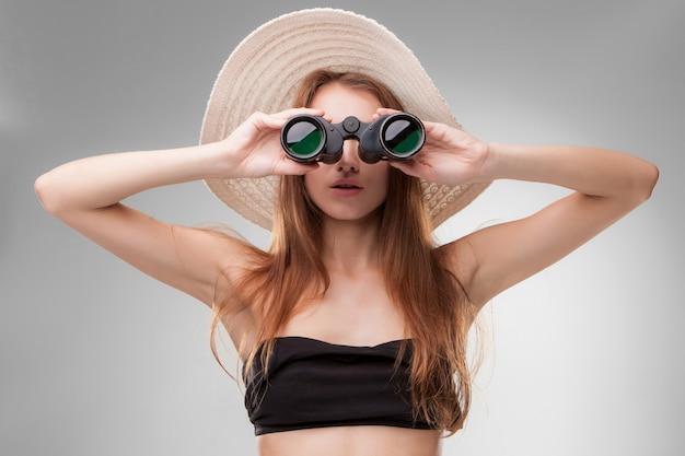 Mujer joven con sombrero con binoculares