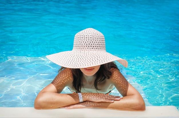 Mujer joven con sombrero blanco descansando en la piscina