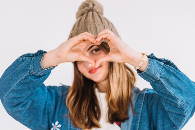 Mujer joven en el sombrero de bobble que muestra símbolo del corazón