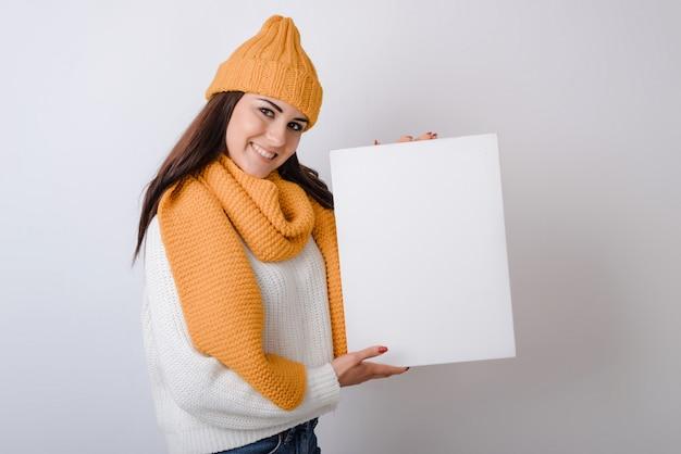 Mujer joven en un sombrero y bufanda sosteniendo una sábana blanca en sus manos sobre un fondo gris