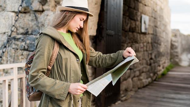 Mujer joven con sombrero comprobando el mapa