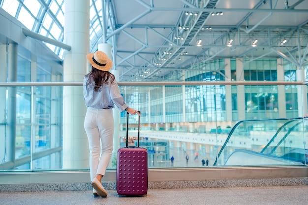 Mujer joven en sombrero con equipaje en aeropuerto internacional.