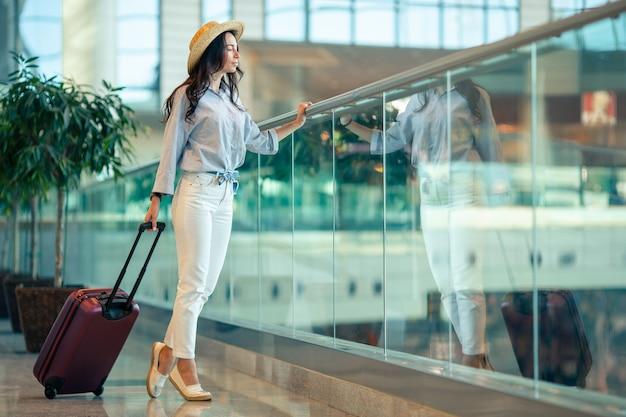 Mujer joven con sombrero con equipaje en el aeropuerto internacional.