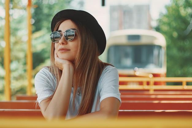 Mujer joven con sombrero y gafas de sol en un city tour