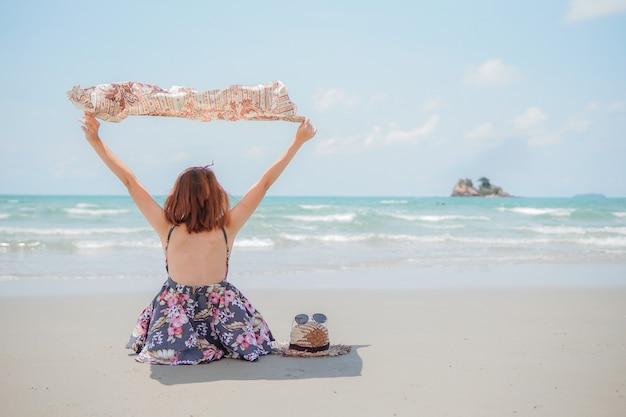 Una mujer joven con sombrero y gafas de sol sentado en la playa