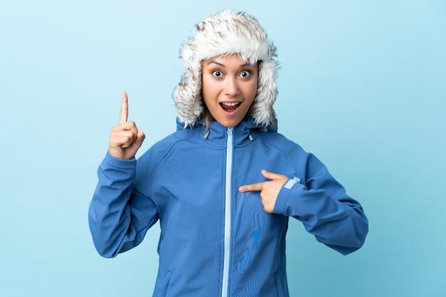 Mujer joven con sombrero de invierno aislado en el espacio azul con expresión facial sorpresa