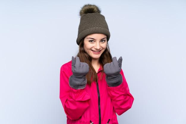 Mujer joven con sombrero de invierno aislado en la pared azul haciendo gesto de dinero