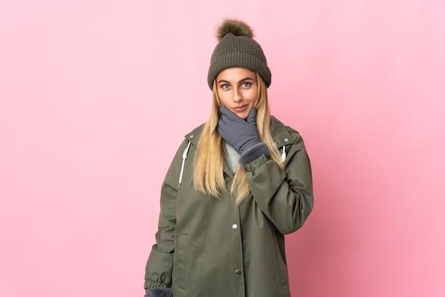 Mujer joven con sombrero de invierno aislado en el pensamiento espacial rosa