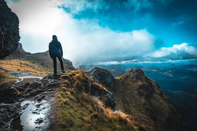 Una mujer joven con sombrero de invierno mirando a la montaña de aiako harriak, oiartzun. país vasco