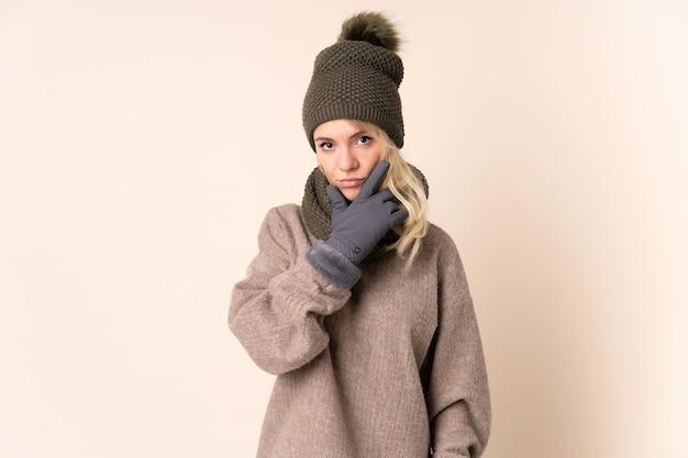 Mujer joven con sombrero de invierno sobre pared aislada pensando en una idea