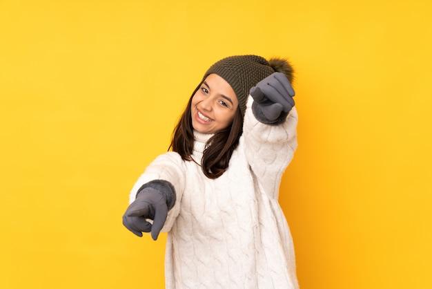 Mujer joven con sombrero de invierno sobre pared amarilla aislada señala con el dedo mientras sonríe