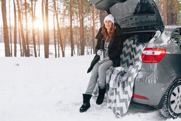 Una mujer joven con sombrero de lana se sienta en el maletero del auto y sostiene una taza de té caliente en sus manos.