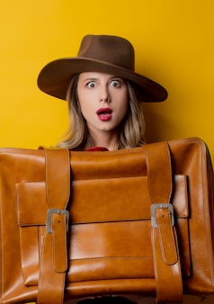 Mujer joven con sombrero con maleta