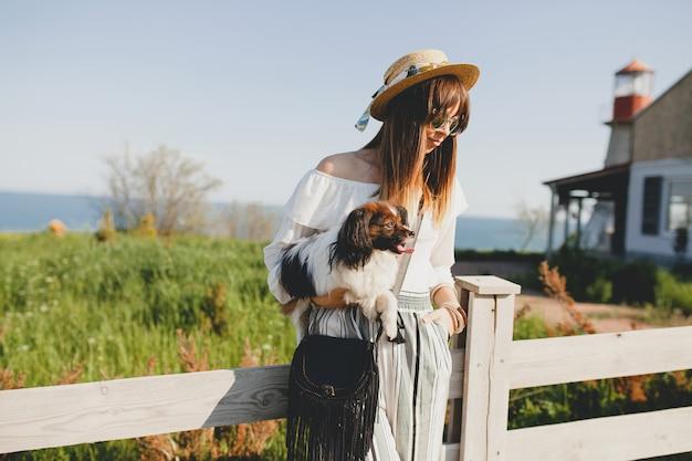 Mujer joven con sombrero de paja con su perro por la valla en el campo