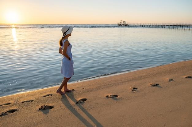 Mujer joven con sombrero de paja y un vestido caminando sola en la playa de arena vacía en la orilla del mar al atardecer.