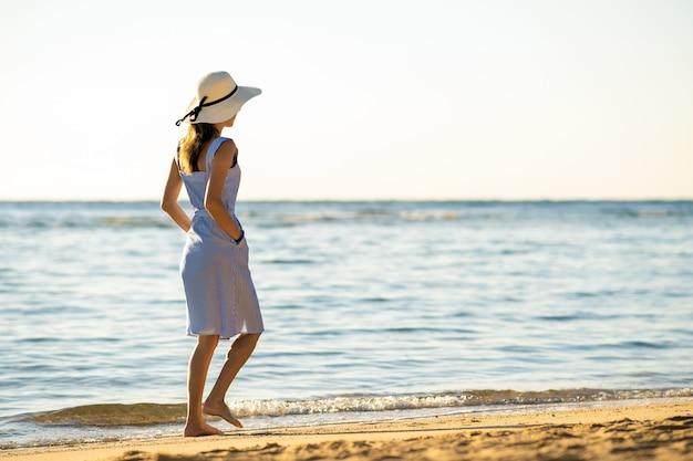 Mujer joven con sombrero de paja y un vestido caminando sola en la playa de arena vacía en la orilla del mar.