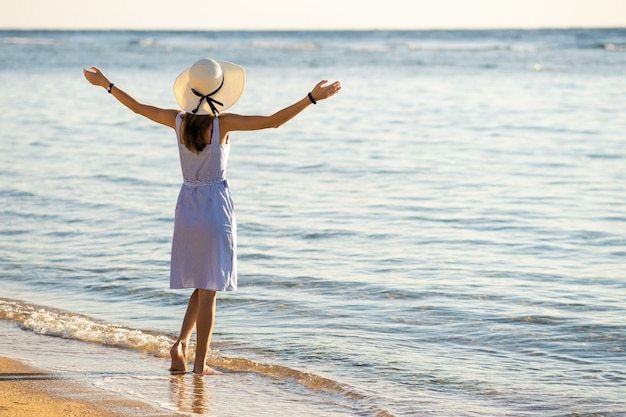 Mujer joven con sombrero de paja y un vestido de pie levantando las manos en la playa de arena vacía en la orilla del mar.