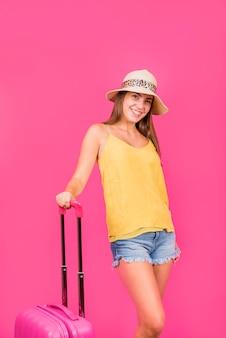 Mujer joven en sombrero de pie y sosteniendo la maleta