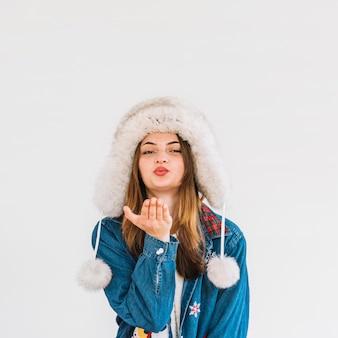 Mujer joven en sombrero de piel enviando beso de aire