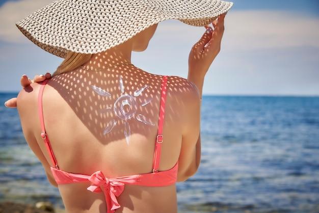 Mujer joven en sombrero con protector solar en la forma del sol en su espalda.