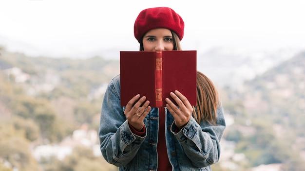 Mujer joven con sombrero de punto sobre su cabeza sosteniendo un libro frente a su boca