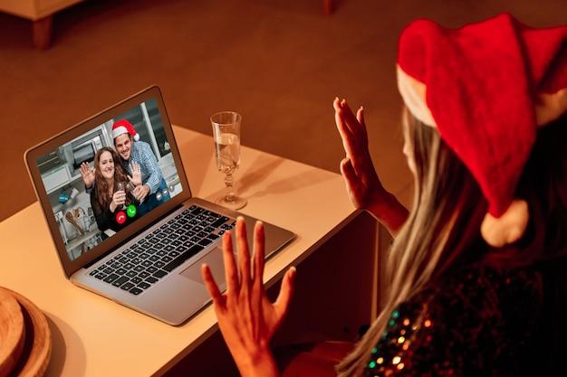 Mujer joven con sombrero de santa claus haciendo una videollamada a su familia para celebrar la navidad.