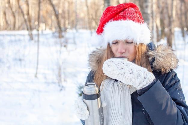 Una mujer joven con un sombrero de santa claus se sirve un té caliente de un termo.