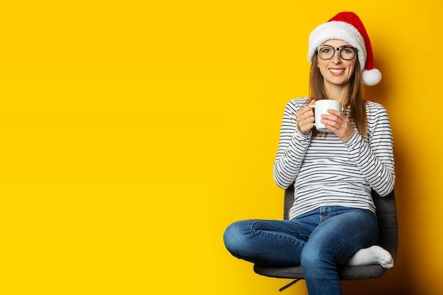 Mujer joven con sombrero de santa se sienta en una silla y sostiene una taza