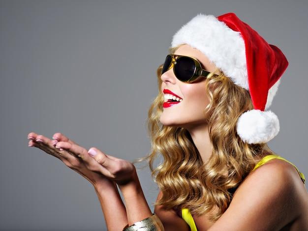 Mujer joven con sombrero de santa tiene algo en la palma posando en el estudio