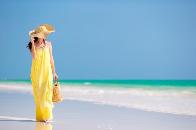 Mujer joven con sombrero durante vacaciones en la playa tropical