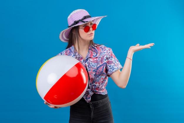 Mujer joven con sombrero de verano con gafas de sol rojas sosteniendo bola inflable mirando a un lado con el ceño fruncido disgustado con el brazo levantado sobre la pared azul