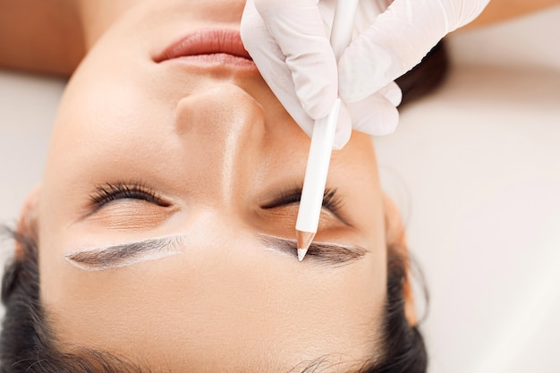 Mujer joven sometida a procedimiento de corrección de cejas en salón de belleza, primer plano