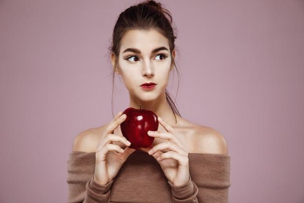 Mujer joven soñadora que sostiene la manzana roja que mira en lado en rosa