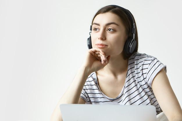 Mujer joven soñadora en ropa casual relajándose en casa, escuchando música usando la aplicación en línea en la computadora portátil