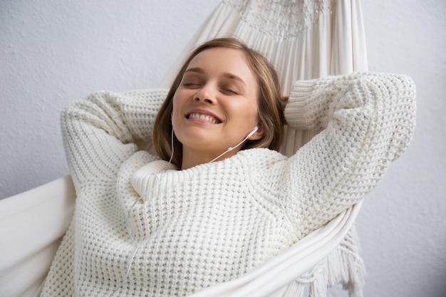 Mujer joven soñadora sonriente que se relaja en hamaca