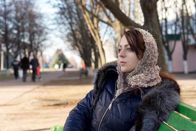 Mujer joven soñando despierto en un banco del parque sentado mirando a lo lejos con una expresión lejana con un pañuelo en la cabeza y una cálida moda de invierno