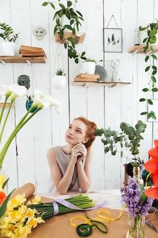Mujer joven soñando mientras trabajaba con flores en el taller