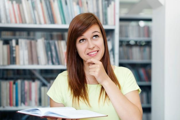 Mujer joven, soñar despierto, en, biblioteca
