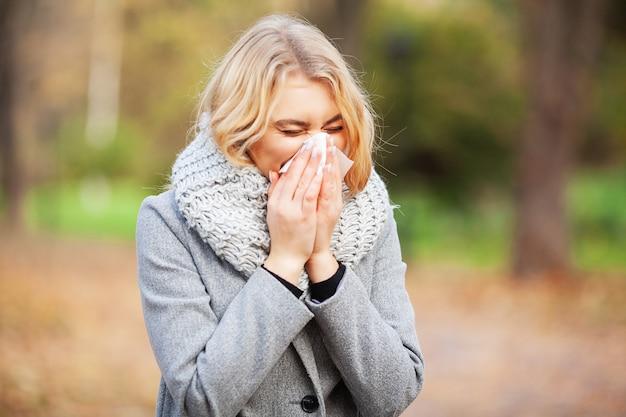 Mujer joven sonarse la nariz en el parque.