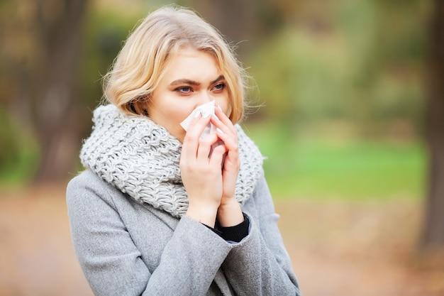 Mujer joven sonarse la nariz en el parque