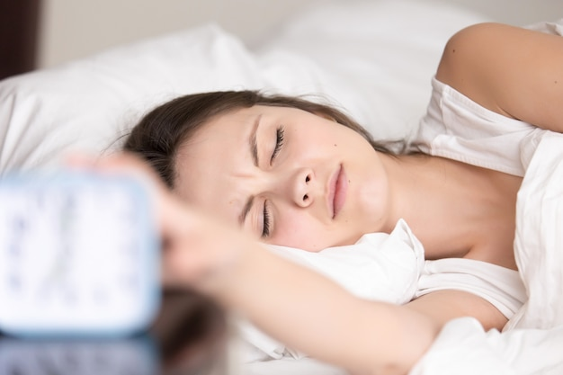 Mujer joven soñolienta apaga la señal del despertador