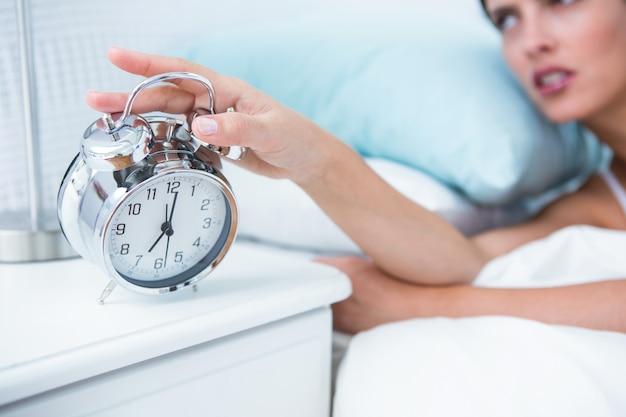 Mujer joven soñolienta en la cama que extiende la mano al despertador