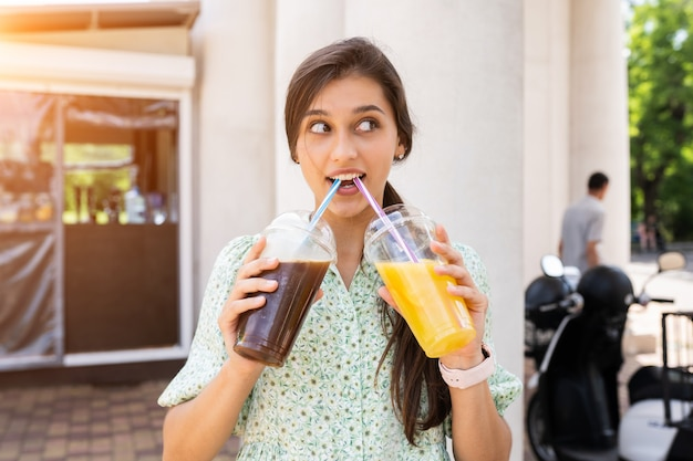 Mujer joven sonriendo y bebe dos cócteles con hielo en vasos de plástico con paja en las calles de la ciudad.