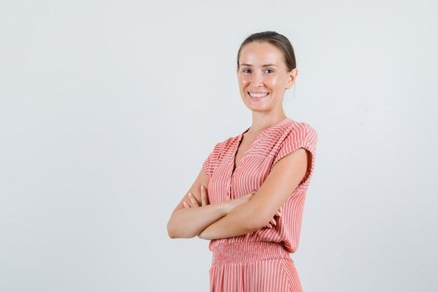 Mujer joven sonriendo con los brazos cruzados en traje de rayas, vista frontal.